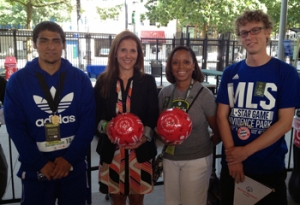 "Santos Lopez (L) of the US and Andrew x of Germany (R) present JoAnn Neale of MLS (2nd from L) and Angela Woods (2nd from R) with ""Play Unified"" balls signed by both squads."